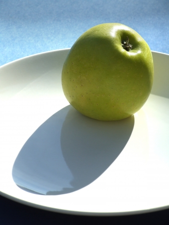 Green apple on a ceramic plate