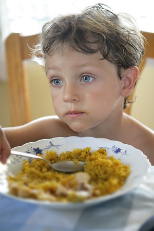 Close up of a blond boy in front of the plate of food