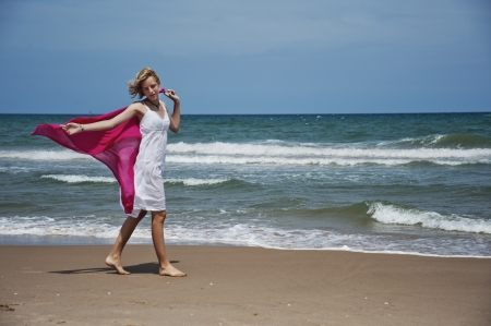 Blonde girl walking along the shore with the wind scarf photo