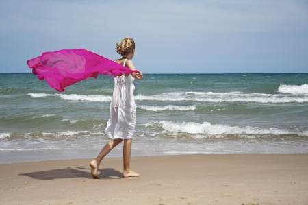 Blonde girl walking along the shore with the wind scarf
