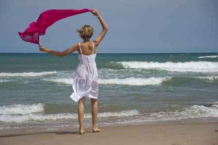 dress blowing in the wind: Blonde girl walking along the shore with the wind scarf