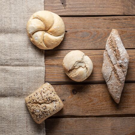 bread with wheat ears and flour on wood board, top view