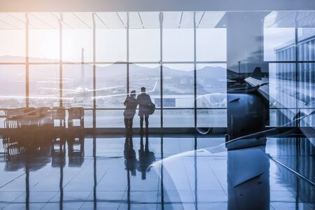 Silhouette of a couple waiting for their flight, watching the planes at the airport. Double exposure.