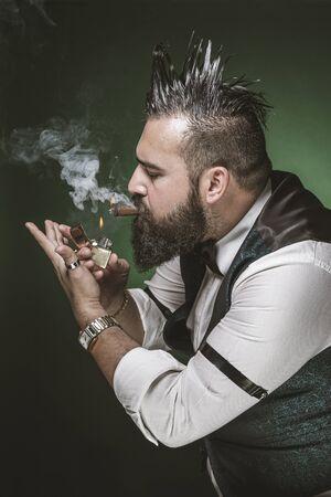 Man with a beard lighting a cigar.