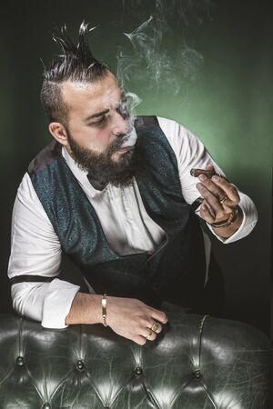 Man with a beard, dressed in a suit and bow tie, looking at a cigar while smoking.