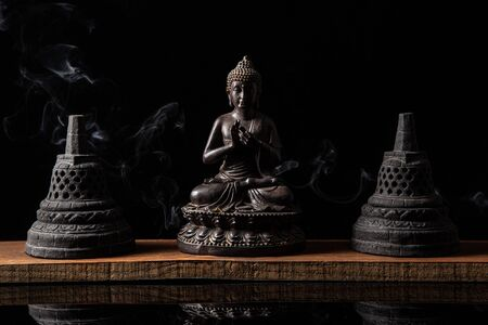 Statue of Buddha sitting in meditation, with buddhist bells and incense smoke. Zen and meditation concept.