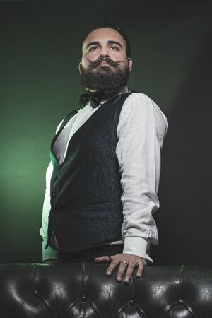 Man with a beard, dressed in a vest and bow tie, standing on a sofa. Reklamní fotografie
