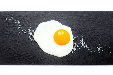 Fried egg on slate plate with salt on white background. Cooking and food concept.