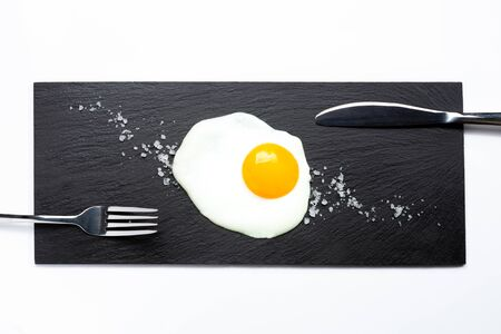 Fried egg on slate plate with knife, fork and salt on white background. Cooking and food concept.