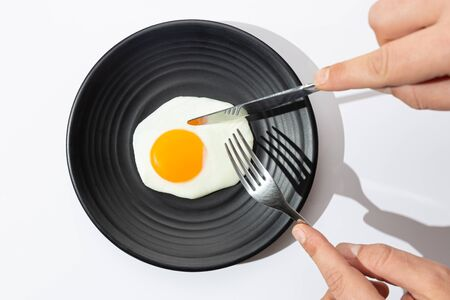 Hands are going to eat with knife and fork a fried egg on black plate on white background.