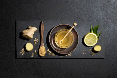 Honey, lemon and ginger on blackboard on black background. Top view. Natural food and brevage concept.