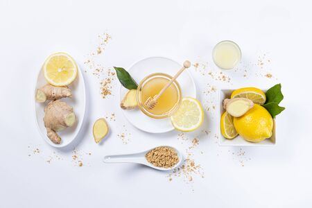 Ginger, honey and lemon, in white plates and spoon on white background. Top view. Natutal food and brevage concept. Stok Fotoğraf