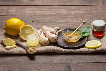 Ginger, honey and lemon, on wooden base. Natutal food and brevage concept.