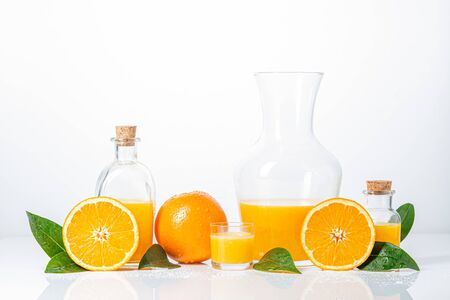 Oranges, oranges slices, orange leaves, and glass containers with orange juice isolated on white background.