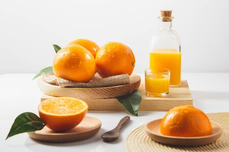 Oranges, oranges slices, orange leaves, and glass containers with orange juice on white background. Stok Fotoğraf
