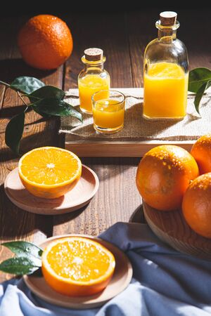 Oranges, oranges slices, orange leaves, and glass containers with orange juice on wooden background. Stok Fotoğraf