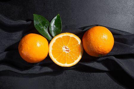 Oranges, orange slice and orange leaves on black textured background