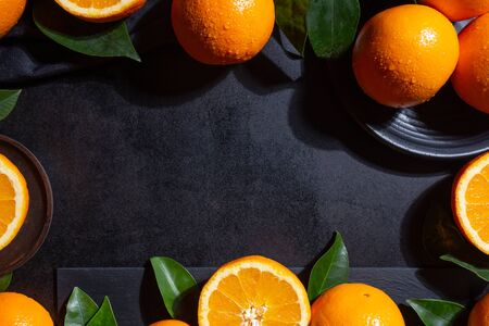 Backgroung with Oranges, orange slices and orange leaves on black textured background