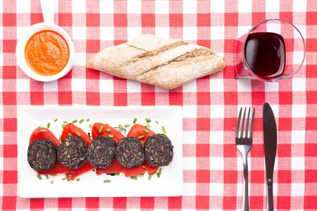 Slices of Spanish black pudding on piquillo peppers in white plate on a red checkered tablecloth. Spanish tapas.