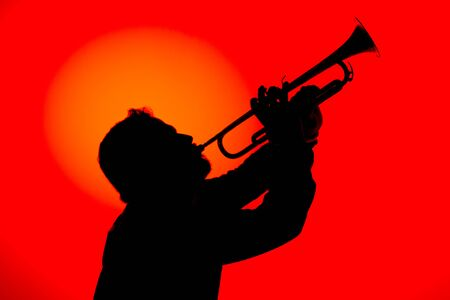 Silhouette of a jazz musician playing trumpet, isolated in red background. Jazz music concept.