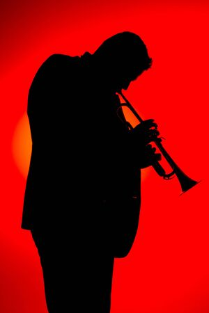 Silhouette of a jazz musician playing trumpet, isolated in red background. Vertical format. Jazz music concept.