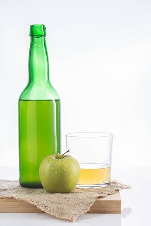 Bottle of Asturian cider with glass and apple on white background.