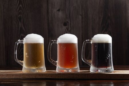 Three kinds of cold beer in jugs on wooden base.