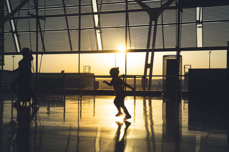 silhouette of an unrecognizable child running through the airport terminal at sunrise. Banque d'images