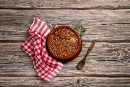 Traditional Spanish dish of lentil stew with chorizo and potatoes on a wooden background. Flat lay composition.