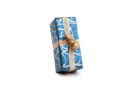 packaged rectangular gift in blue packaging with gold bow and gold pattern on a white background Stock Photo