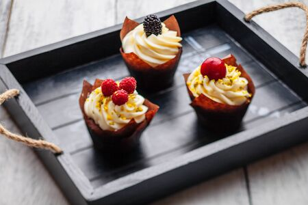 muffins with Belgian chocolate and white chocolate cream and mascarpone with berries on a wooden tray