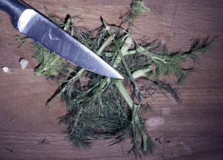 Fennel leaves on the wood board cut with a knife