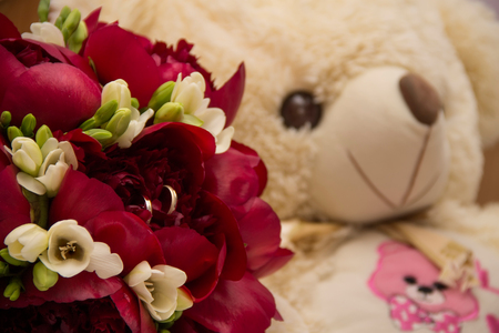 Wedding rings standing on a bouquet of peonies and freesias and a teddy bear Stock Photo