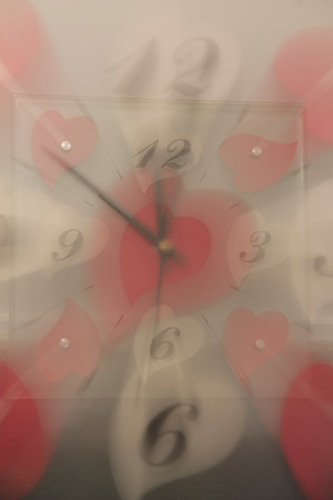 Double exposure of a clock with white and red hearts Stockfoto