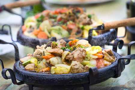 Delicious warm food with pork meat, onions, green squash, carrots and other vegetables Stock Photo