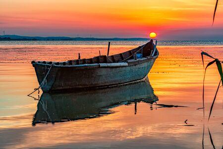 Beautiful sunrise with a boat on the lake, Razelm Razim Lake, Sarichioi, Romania