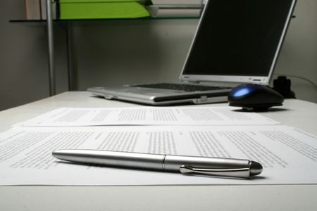 desk tidy: White office desk with a laptop, printed documents and a pen. Darker business background.