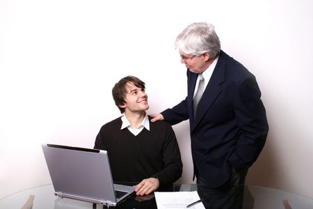 dad son: Business Junior and Senior and a glass desk with laptop on it.