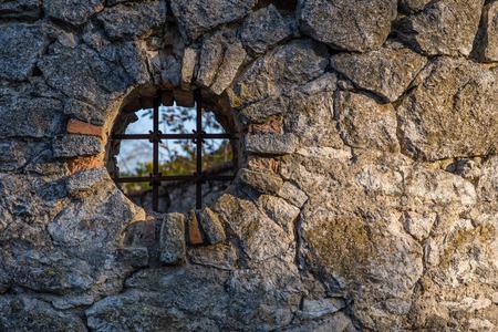 lattice window: Round shaped window with a lattice in a stone fence. Round window. Window in a fence.