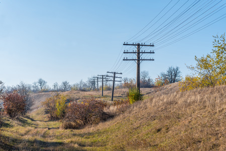 crooked: Old crooked outdated telegraph poles under blue sky in autumn. Crooked buddyies. Not really straight line.