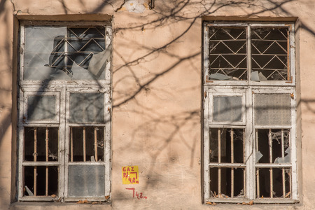 Two windows with shuttered glass in an abandoned building. Without tenants. Abandoned house.
