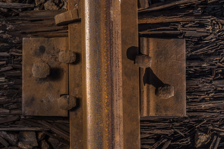 sleeper: Rusty rails crammed into a rotten sleeper.