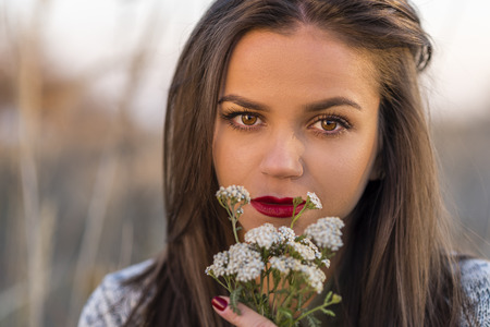 bouquet fleurs: Sad autumn look. Portrait of a nice teenager girl holding small bouquet in a autumn field. Girl has brown eyes and hair and red lips. Banque d'images