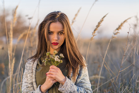 A beautiful teenage girl sitting sad in a field with a bouquet of field flowers in hands at autumn sunset. Girl has brown eyes and hair and red lips.