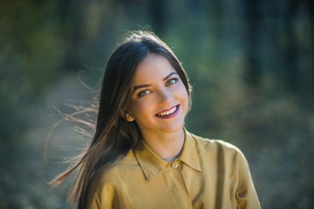 cabello rubio: Portrait of smiling girl with bright eyes. Portrait of a beatiful smiling teenager girl with bright eyes wearing yellow shirt in the woods. Warm autumn afternoon.