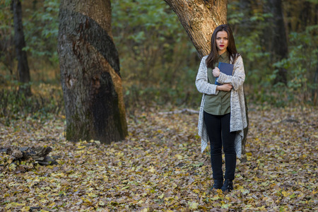 young tree: Scared by reading fairytales. A teenager girl is holding a book in an evening forest with two oak trees in the background. She is standing on foliage. The girl has a serious expression on her face.