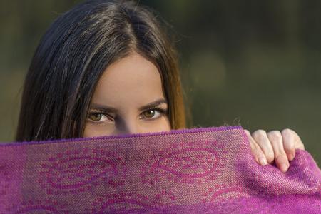 자주색 스카프 위의 눈. 갈색 눈을 가진 꽤 십 대 소녀는 오후 숲에서 보라색 스카프와 함께 그녀의 얼굴을 덮고있다. 필드의 얕은 깊이.