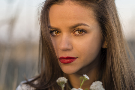 Autumn look. Portrait of a nice teenager girl holding small bouquet in a autumn field. Girl has brown eyes and hair and red lips.