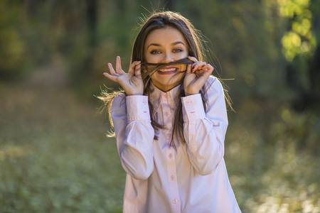 eyes wide: A teenage girl is making mustache from her hair with eyes wide open and a happy expression on her face. Stock Photo