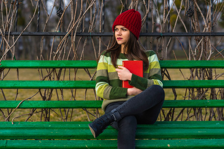 medium shot: Teenager girl in red hat and green sweater sitting on a bench in a park and holding a red book. Medium shot.